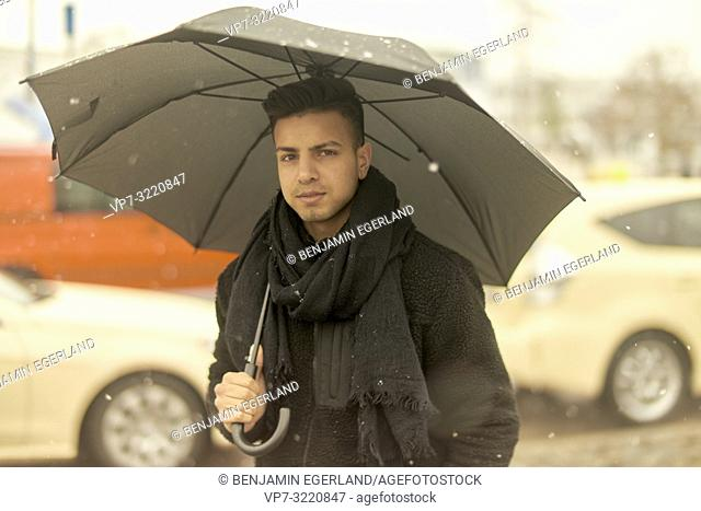 young man, Afghan ethnicity, with umbrella outdoors in city during winter, snowing, in Munich, Germany