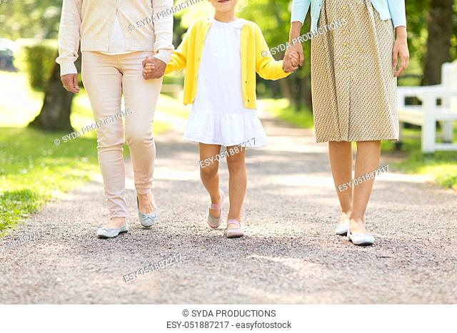 mother, daughter and grandmother walking at park