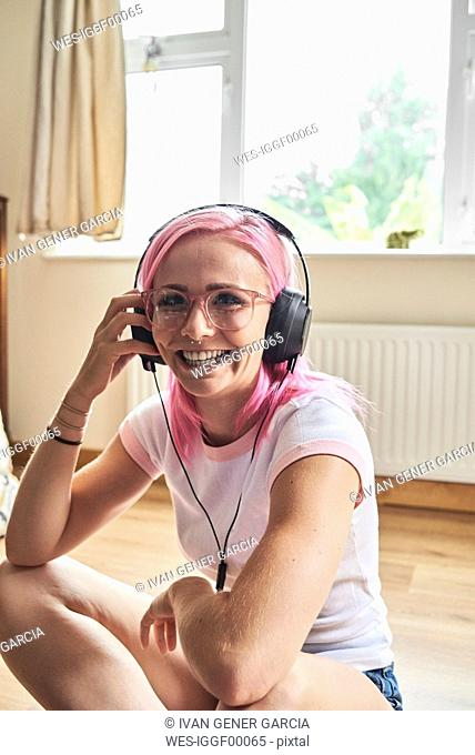 Happy young woman with pink hair listening to music