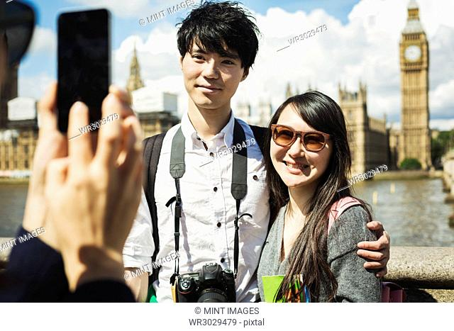 Smiling woman with black hair taking picture of couple with smartphone, standing on Westminster Bridge over the River Thames, London