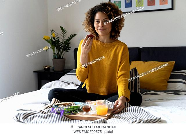 Woman sitting on bed, having a healthy breakfast