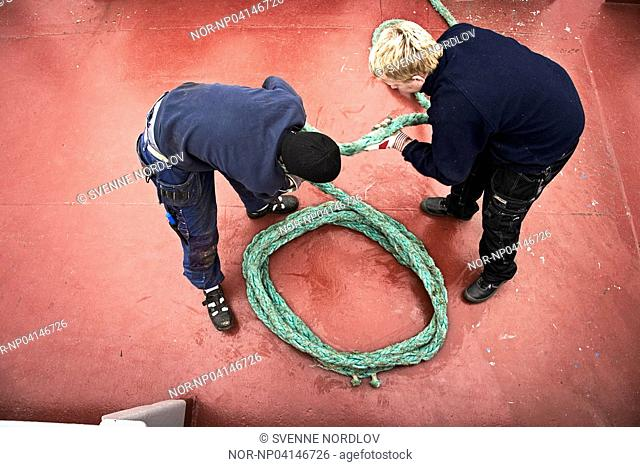 Sailors onboard a ship with a rope