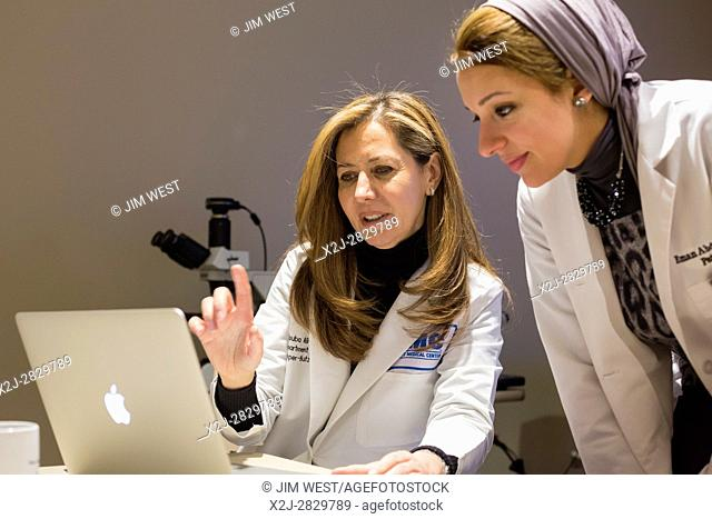 Detroit, Michigan - Dr. Rouba Ali (left), a pathologist, teaches a class at the Detroit Medical Center. Dr. Eman Abdulfatah, a pathology resident, watches