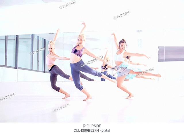 Young female ballet dancers practicing in dance studio, dancing on one leg