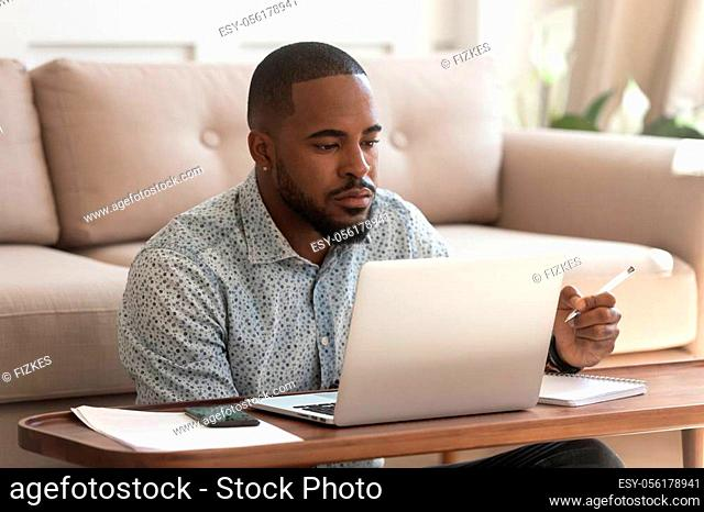 Concentrated african American male student look at laptop screen studying at home make notes in notebook, focused biracial man watch online learning course or...