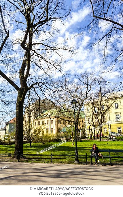 A woman resting on a bench at Planty, well known park around Old Town in Krakow, Poland, Europe