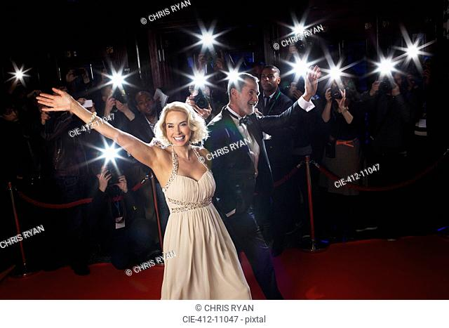 Well dressed couple waving to paparazzi on red carpet