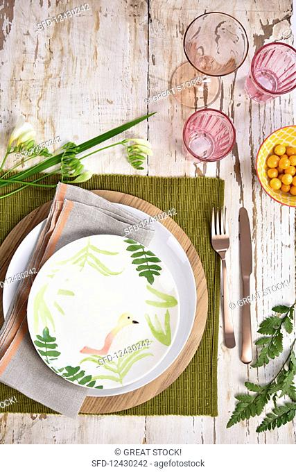 An Icelandic-style place setting with a wooden platter and a bird pattern