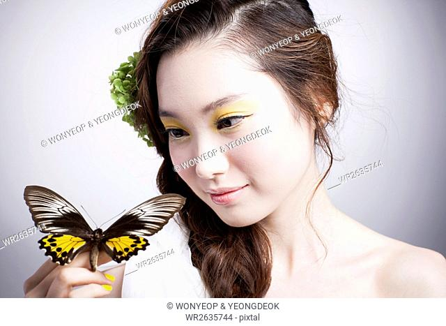 Portrait of young Korean woman with long wavy hair nad in yellow eye sha posing with a butterfly