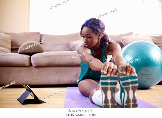 Young woman exercising on sitting room floor whilst looking at digital tablet