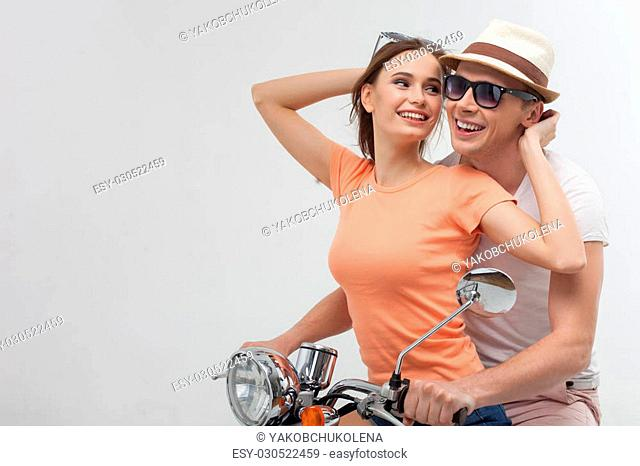 Lets travel together. Portrait of beautiful loving couple enjoying their trip on the scooter in summer. The woman is looking at the man with love