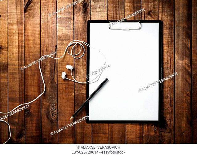 Clipboard with blank white paper, letterhead, pencil and headphones on vintage wooden table background. Mock-up for branding identity for designers