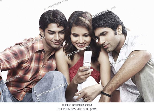 Close-up of a young woman and two young men looking at a mobile phone