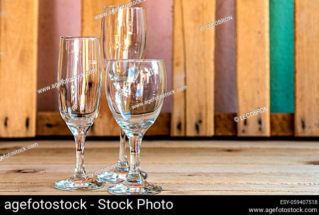 Glass bowls. Glasses for serving wine. Crystals on the aged wooden background. Table and kitchen utensils