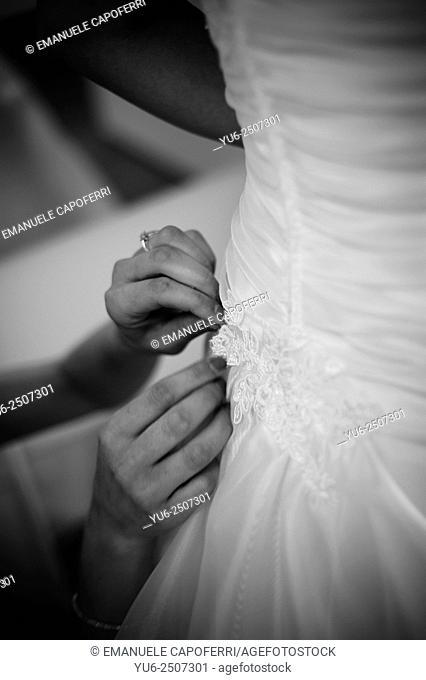 Hands close bride's dress