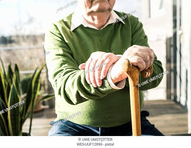 Senior man sitting at the window leaning on cane
