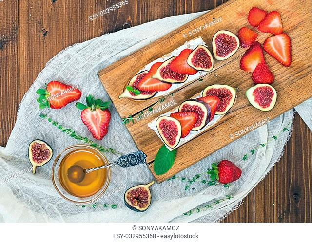 Fresh strawberries, figs, mint leaves, thyme and a small bawl of honey ob a wooden cutting board over a piece of linen fabric and medium-dark wooden background