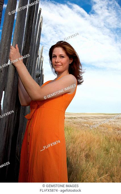 Young Woman in Orange Dress Next to Prairie Fence, South of Medicine Hat, Alberta