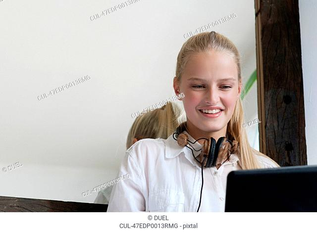 Smiling woman in headphones using laptop