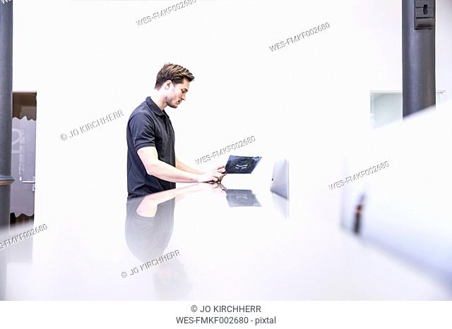 Dentist looking at x-ray image, standing at reception