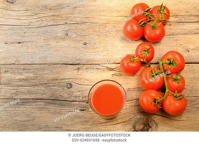 freshly organic harvested and wet tomatoes and juice on a rustic, wooden kitchen table