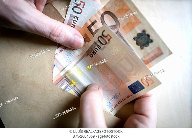 Hands of a woman with fifty euro notes