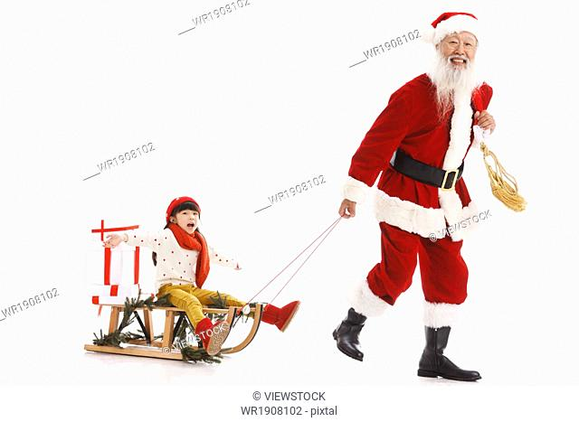 Santa Claus took the little girl sat on a sled