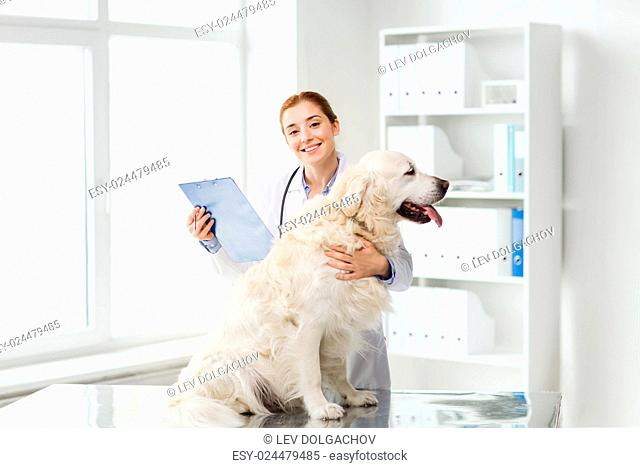 medicine, pet, animals, health care and people concept - happy veterinarian or doctor with golden retriever dog and clipboard at vet clinic