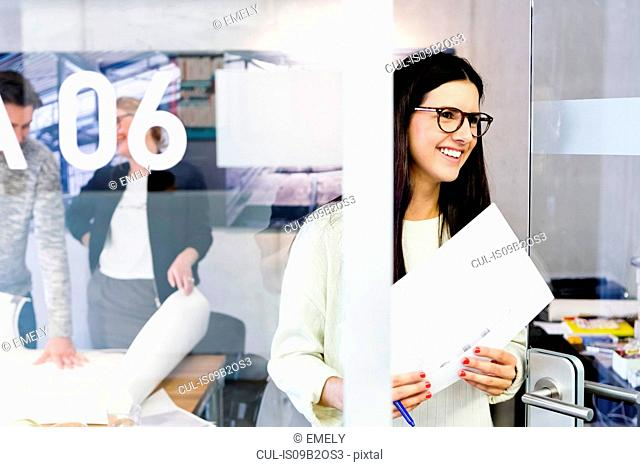 Young woman in office holding paperwork looking away smiling