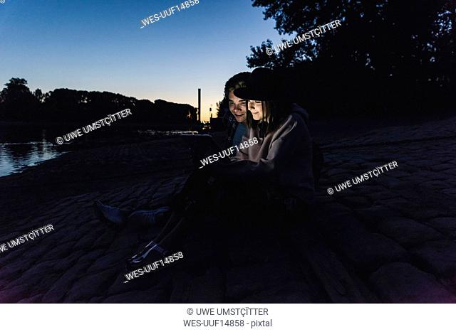 Young couple using tablet at the riverside in the evening
