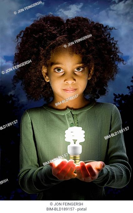 African girl holding glowing cfl lightbulb