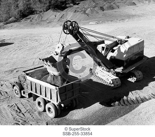 Excavator loading rock dirt into a dump truck
