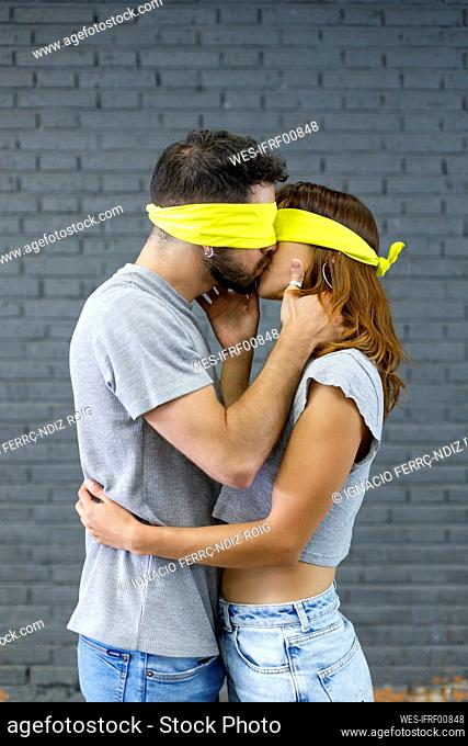 Affectionate couple with eyes covered with cloth kissing each other by gray wall