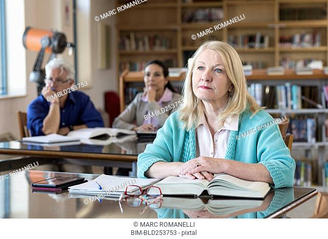 Curious older woman listening in library