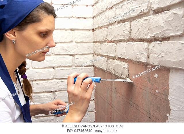 Girl plasterer lays on the wall with plaster imitation brickwork