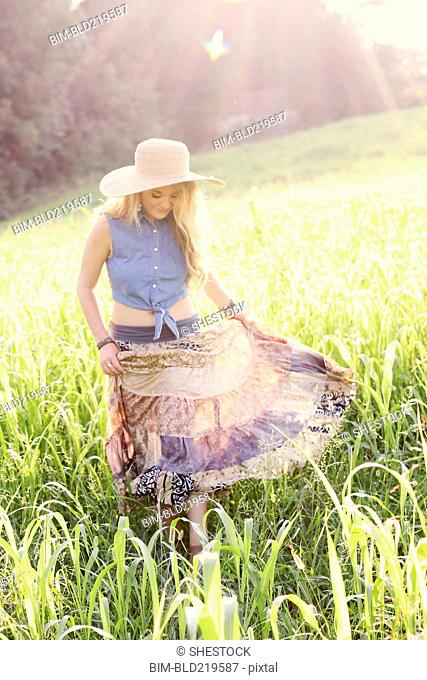 Teenage girl walking in tall grass