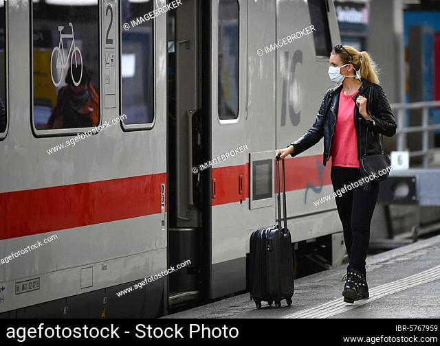 Woman with face mask, waiting for train, corona crisis, main station, Stuttgart, Baden-Württemberg, Germany, Europe