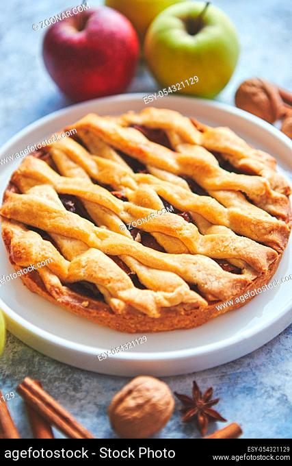 Fresh and tasty sweet homemade apple pie cake with cinnamon sticks, walnuts and apples on side. Placed on stone background