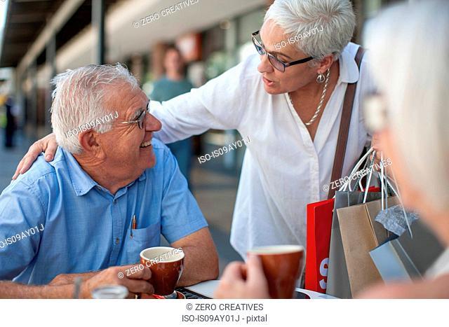 Woman shopper greeting senior man at sidewalk cafe