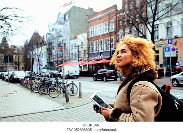 young pretty african american girl with curly hair making photo on a tablet, lifestyle people concept, tourist in european german city close up