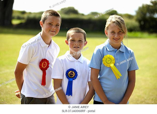 Children wearing ribbons in field