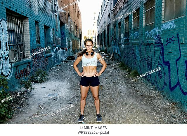 Female athlete standing on street lined with buildings covered in graffiti
