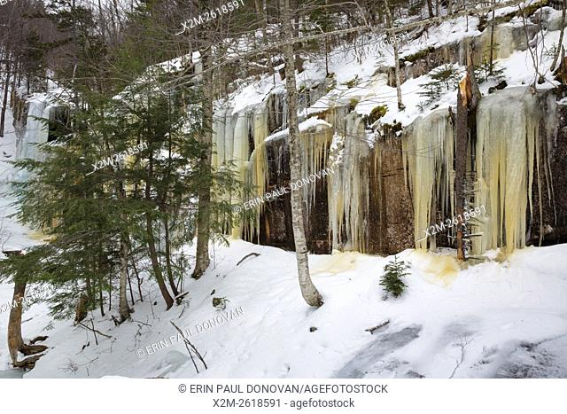Ice build up next to Pitcher Falls (in the back) during the winter months in Albany, New Hampshire USA. This waterfall is located next to Champney Falls along...