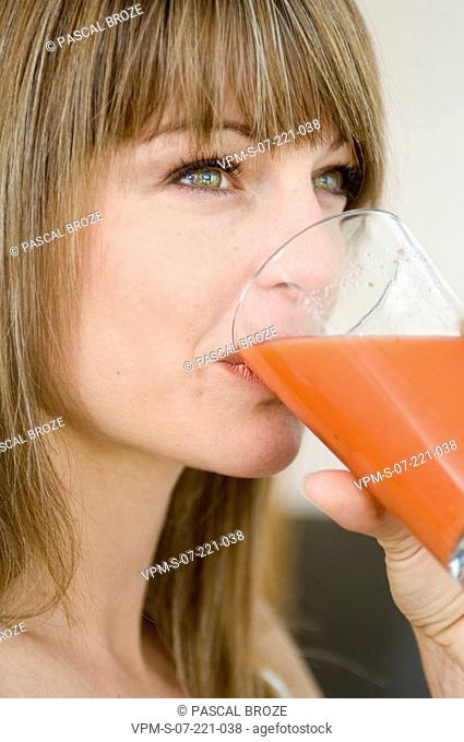 Close-up of a young woman drinking juice