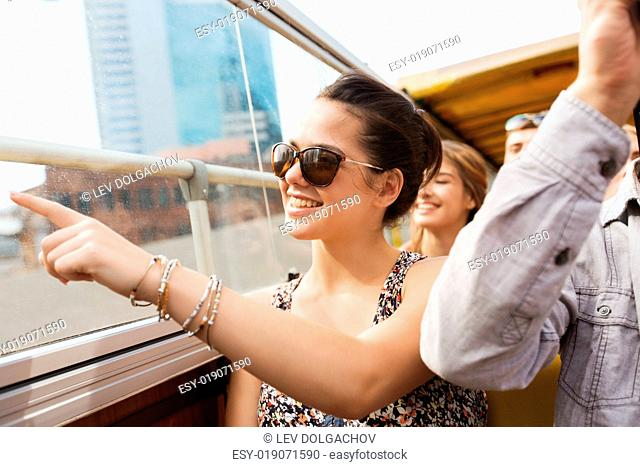 travel, tourism, summer vacation, sightseeing and people concept - happy teenage girl in sunglasses with group of friends traveling by tour bus