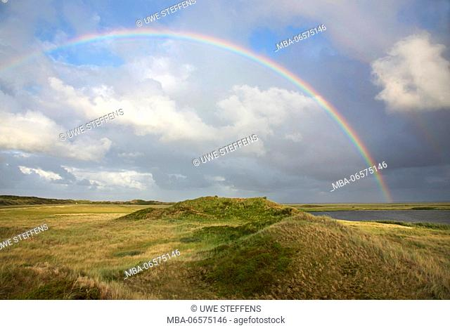 Rainbows above the green dunes at the Schloppsee on the island Langeoog