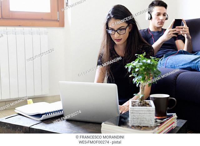 Young woman using laptop in the living room while her boyfriend sitting on the couch with cell phone