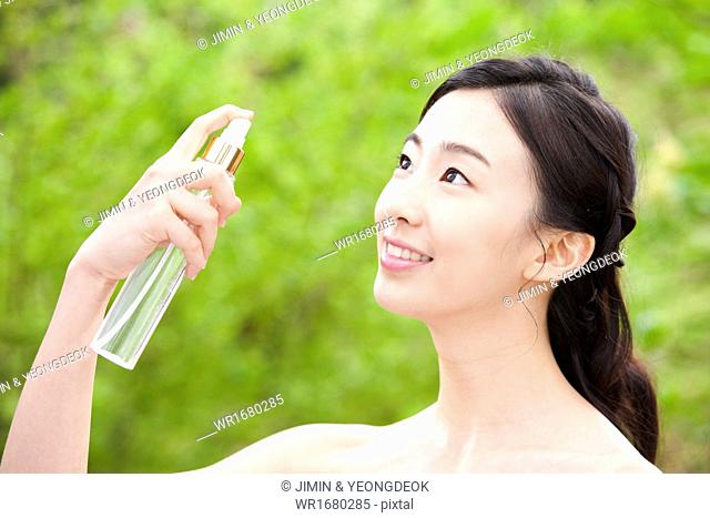 a woman holding a cosmetic bottle in the nature