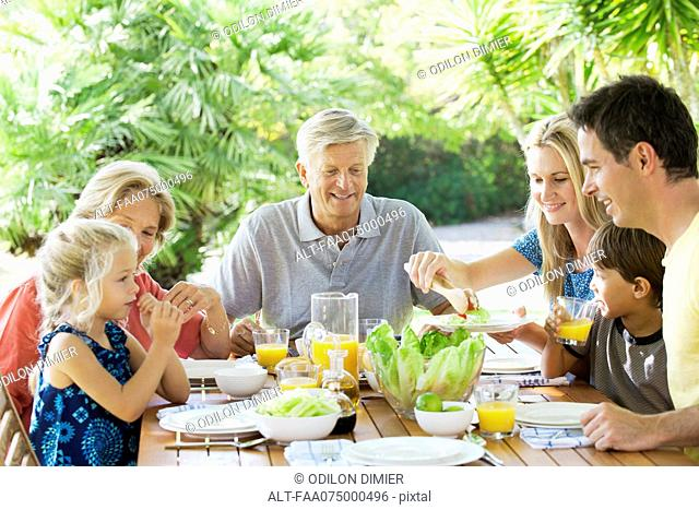 Multi-generation family having breakfast together outdoors