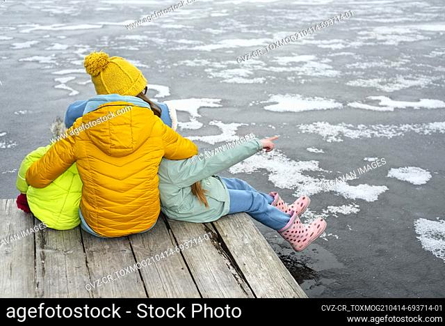 Mom with children sits on a wooden bridge by a frozen lake